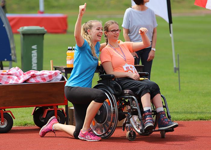 Beweegcoach Ilvy juichend op de foto samen met een vrouw in een rolstoel