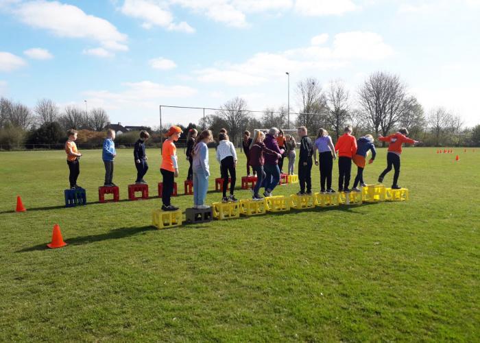 Kinderen die in een oranje shirt buiten spellen spelen tijdens de Koningsspelen