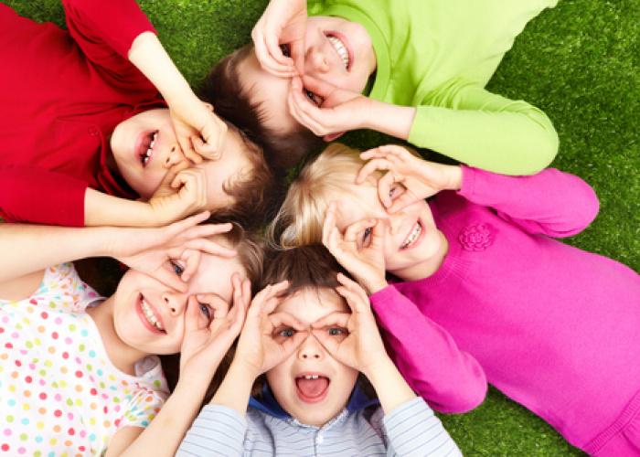 Kinderen die in een rondje op het grasveld liggen en met hun handen een brilletje maken