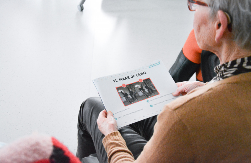 Een vrouw met een boekje vol beweegoefeningen van Iedereen Doet Mee op haar schoot