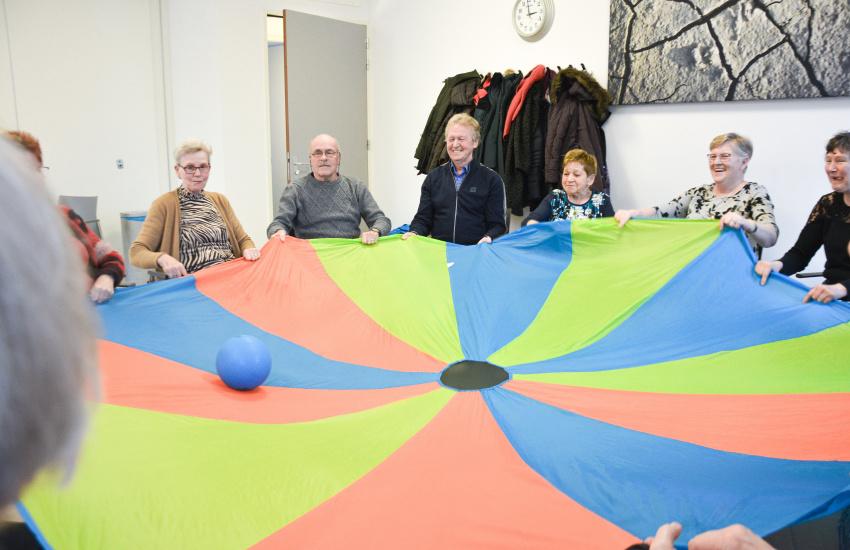 Ouderen die in een kring zitten een groot rond doek vasthouden met een bal in het midden