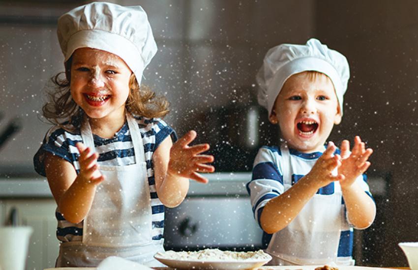 Kinderen die aan het koken zijn met een koksmuts op