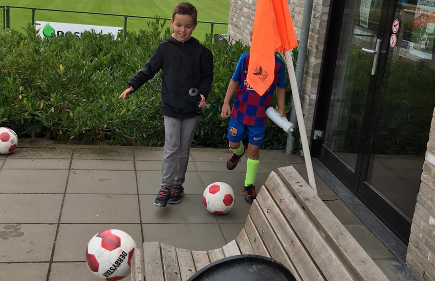 Kinderen die een bal in een ton proberen te trappen