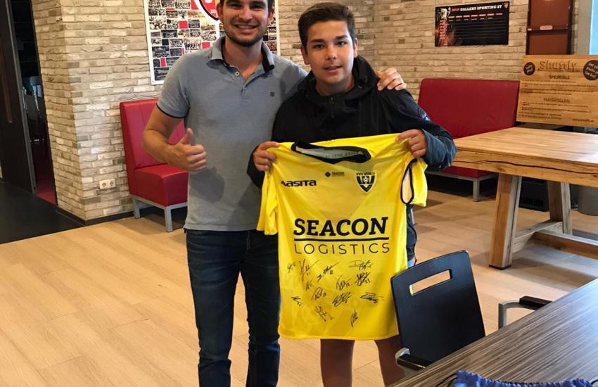 Beweegcoach Joey houdt samen met een kind een gesigneerd shirt van VVV Venlo omhoog